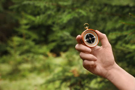 Woman checking modern compass in wilderness, closeup with space for text Stock Photo