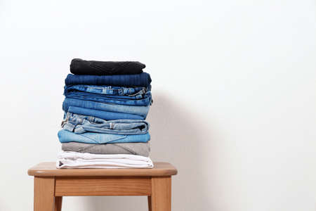 Stack of different jeans on table against white background. Space for text Stock Photo