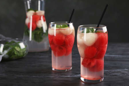 Glasses with tasty melon and watermelon ball drinks on dark table