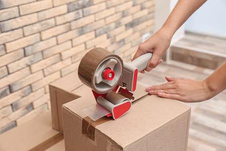 Woman packing carton box indoors, closeup. Moving day Stock Photo
