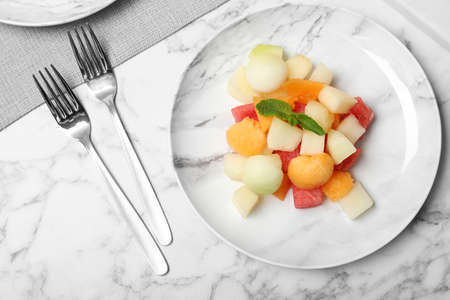 Salad with watermelon and melon on marble background, flat lay Stock Photo