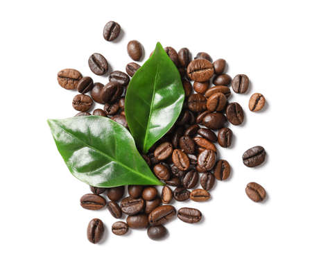 Roasted coffee beans and green leaves on white background, top view