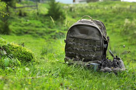 Backpack and hiking boots in green mountain valley. Summer camping