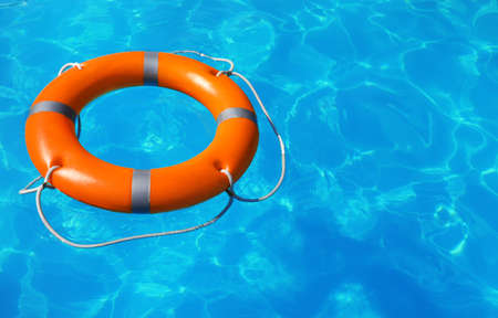 Lifebuoy floating in swimming pool on sunny day. Space for text Stock Photo