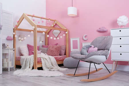 Childs room interior with comfortable bed and garland Stock Photo