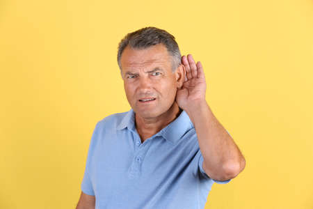Mature man with hearing problem on color background