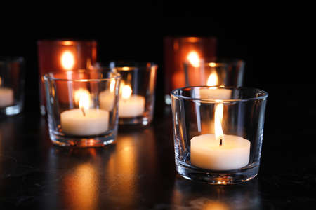 Burning candles on table in darkness, space for text. Funeral symbol