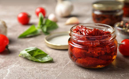 Dried tomatoes in glass jar on table. Healthy snack