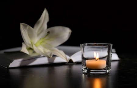 Brennende Kerze, Buch und weiße Lilie auf Tisch in der Dunkelheit, Platz für Text. Begräbnissymbol Standard-Bild