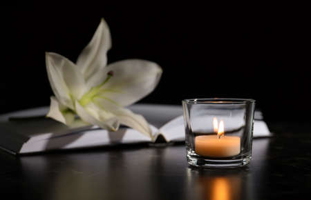 Burning candle, book and white lily on table in darkness, space for text. Funeral symbol 스톡 콘텐츠