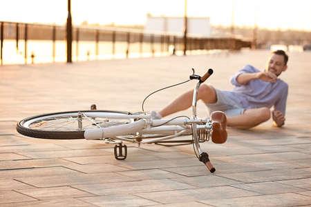 Man fallen off his bicycle on street, focus on bike