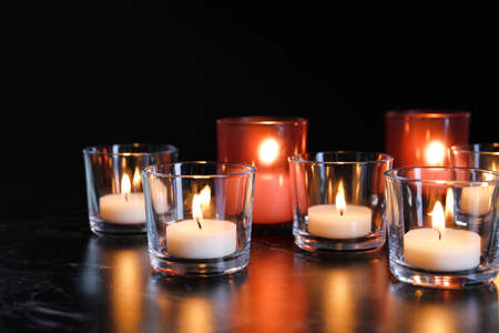 Burning candles on table in darkness. Funeral symbol