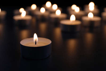 Burning candle on table in darkness, closeup with space for text. Funeral symbol Stock Photo