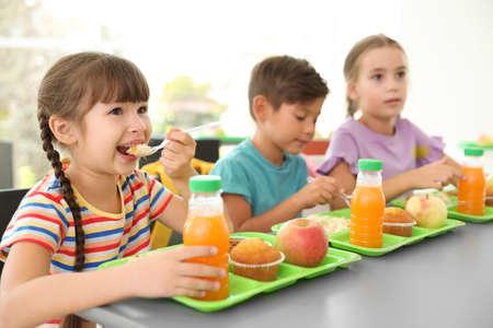 Kinder sitzen am Tisch und essen gesundes Essen während der Pause in der Schule
