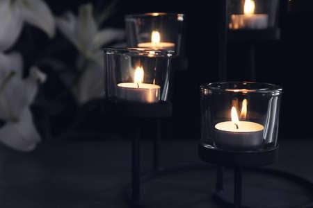 Burning candles on dark background. Funeral symbol