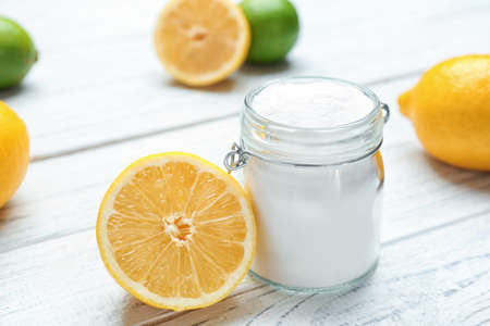 Jar with baking soda and lemon on white wooden table Banco de Imagens