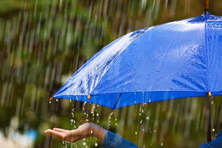 Mujer con paraguas brillante bajo la lluvia en la calle, primer plano