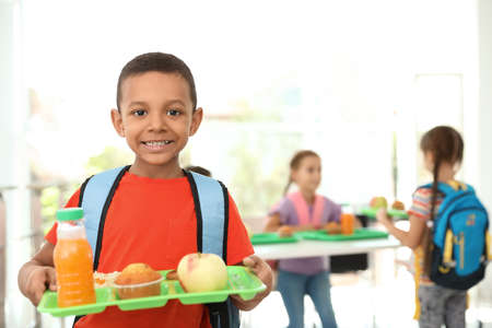 African-American boy holding tray with healthy food at school canteen Stockfoto