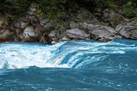 Mountain river flowing along rocky banks in wilderness Stock Photo
