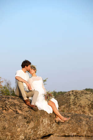 Happy newlyweds with beautiful field bouquet sitting on rock outdoors