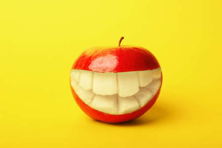 Funny smiling apple on color background