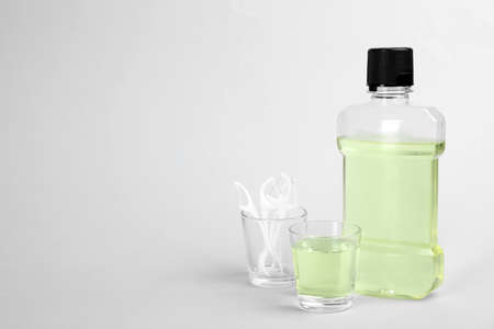 Mouthwash, dental floss and space for text on light background. Teeth care