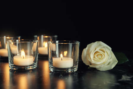 White rose and burning candles on table in darkness. Funeral symbol Stock Photo