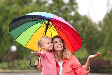 Happy mother and daughter with bright umbrella under rain outdoors Foto de archivo