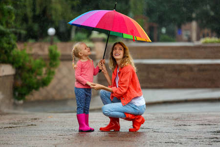 Happy mother and daughter with bright umbrella under rain outdoors Banque d'images