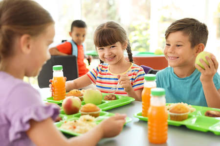 niños sentados en la mesa y comer comida sana durante el descanso en la escuela