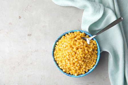 Flat lay composition with corn kernels in bowl on grey background. Space for text