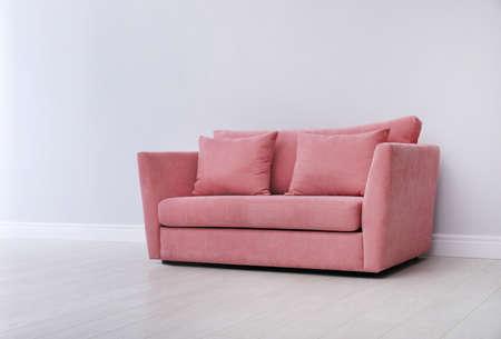 Room interior with comfortable sofa near white wall Stock Photo