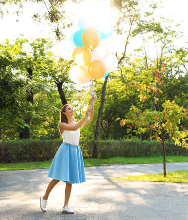 Beautiful teenage girl holding colorful balloons in park