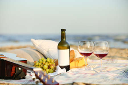 Blanket with food, wine and guitar on beach. Romantic picnic for couple Stock Photo