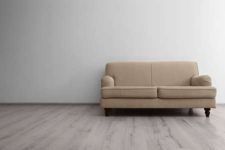 Room interior with comfortable sofa near white wall. Space for text Stock Photo