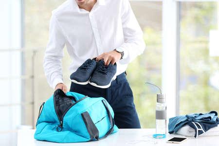 Joven empresario de embalaje material deportivo para entrenamiento en bolsa en la oficina