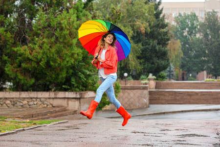 mujer joven feliz con paraguas brillante bajo la lluvia al aire libre