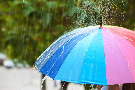 Person with bright umbrella under rain on street, closeup Banque d'images