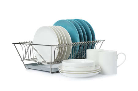 Rack with dishes and clean tableware on white background