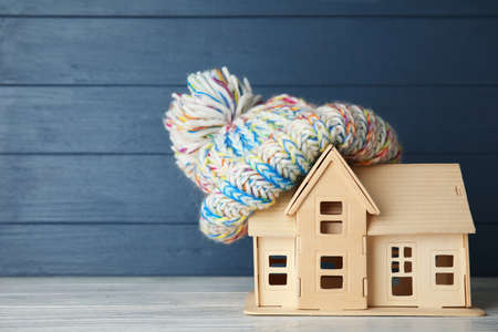 Plywood toy house with warm hat and space for text against color background. Heating system