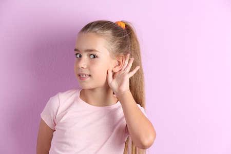 Jolie petite fille avec problème auditif sur fond de couleur