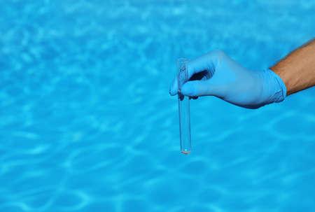 Homme tenant un tube à essai avec de l'eau contre la piscine aux beaux jours. Espace pour le texte