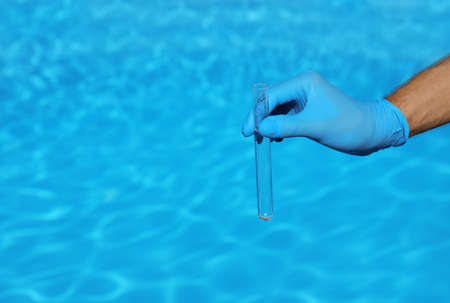 Man holding test tube with water against swimming pool on sunny day. Space for text