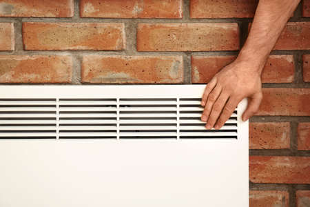 Man checking temperature of heating convector on brick, closeup