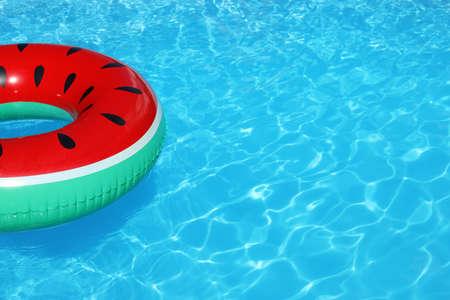Opblaasbare ring drijvend in zwembad op zonnige dag. Ruimte voor tekst