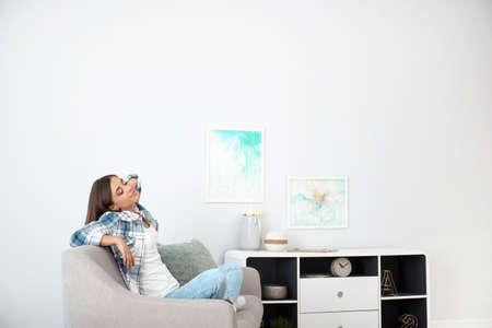 Jeune femme, délassant, sous, climatiseur, chez soi