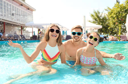 Happy family in pool on sunny day Stock Photo
