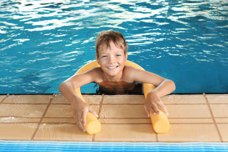 Little boy with swimming noodle in indoor pool
