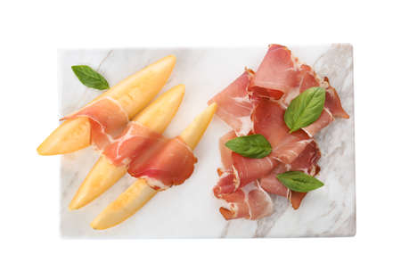 Board with melon slices and prosciutto on white background, top view