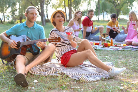 Young man playing guitar for his girlfriend in park. Summer picnic